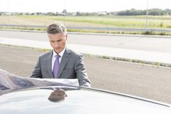Serious businessman reading map outside car while standing on road stock images