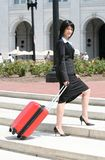Business Trip: Woman Traveling. Business woman on a trip, traveling, city street, red suitcase Stock Photography