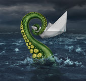 Business Trouble. And financial trap concept as an origami paper boat in a stormy sea being trapped by a monster tentacle squeezing the victim as a metaphor for Stock Images