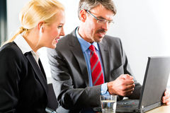 Businesspeople looking at laptop in consultation Royalty Free Stock Images