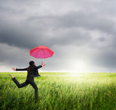 Business umbrella woman jumping to riancloud  in grassland with red umbrella Royalty Free Stock Images