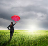 Business umbrella woman standing to riancloud  in grassland with red umbrella Stock Photography