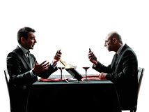 Business using smartphones dinner silhouettes Stock Photos