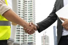 Business Venture,  Businessmen collaborate with engineers. Close up of business people handshake on big city background, Business Venture, Businessmen Stock Image