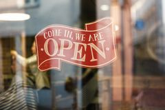 Business vintage sign that says Come in We`re Open on barber and hair salon shop window - Image of abstract blur stock photo