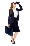 Business vision. Concept with businesswoman looking through binoculars while wearing a suit and with briefcase isolated on white stock images