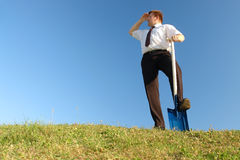 Business vision. Businessman in white shirt and tie standing in grass field over clear blue sky with one leg resting on shovel driven into grass looking sideways stock photos