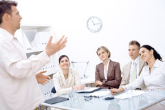 Business vision. Businessman standing and explaining to four colleagues sitting in front of royalty free stock image