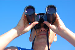 Business vision. Man with the binoculars over blue sky Royalty Free Stock Photography
