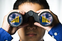 Business vision. A businessman looking through binoculars, seeing conflicting trends in earnings prediction, can be used for business vision or business royalty free stock photos