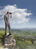 Business vision. Businessman standing at the edge of a cliff looking through binoculars concept for job search, business vision or looking to the future