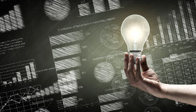 Business vision. Close up of hand holding light bulb with sketches at background Royalty Free Stock Images