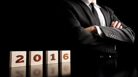 Business vision for the coming year 2016. 2016 sign spelled over wooden cubes with businessman confidently standing next to it, over black background stock photography