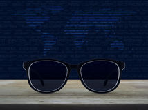 Business vision concept, Elements of this image furnished by NAS. Black eye glasses on wooden table over world map and computer binary code blue background Royalty Free Stock Photos