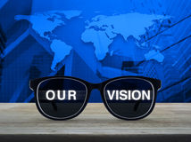 Business vision concept, Elements of this image furnished by NAS. Black glasses with our vision text on wooden table over world map and city tower, Business Stock Photo