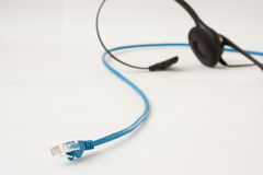 Business VOIP headset. Blue Ethernet cable with business headset in the background Stock Photos