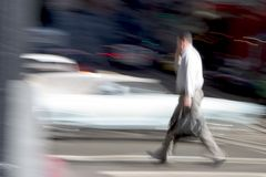 Business Walk. A business man walks across the street briskly while talking on a cell phone. An intensionally long shutter gives a blurred sense of urgency to stock image
