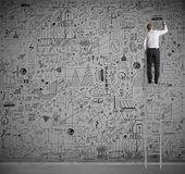 Business on wall. Businessman on a scale drawing on wall Stock Image