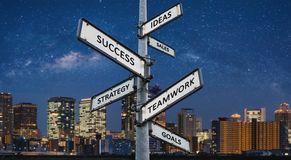 Business ways to success on directional signpost, city at night background royalty free stock image