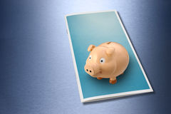Business Wealth Brochure Piggybank. A blank brochure with a piggybank on top with a blue metallic background Stock Photography