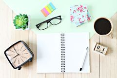 Top view or flat lay of open notebook paper, accessories, cube calendar and coffee cup on wooden background Stock Images