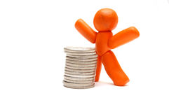 BUSINESS WINNER. Plasticine figure staying in front of coins pile. Winner in business Stock Photo