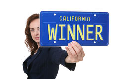 Business Winner. A pretty business woman holding a winner license plate Stock Photo