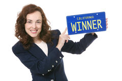 Business Winner. A pretty business woman holding a winner license plate Royalty Free Stock Photography
