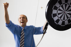 Business winner achieved goal. Happy businessman cheering as he hit the target with bow and arrow symbolizing successful business Stock Photography
