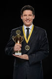 Business winner. Happy businessman holding a trophy while standi Stock Photo