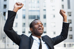 Business winner. Happy young African man in formalwear keeping arms raised and expressing positivity while standing outdoors royalty free stock photography