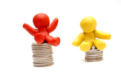 BUSINESS WINNER AND LOSER. Plasticine figures sitting on coins piles. Winner and loser in business Royalty Free Stock Images