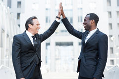 Business winners. Two cheerful business men clapping each other hands and smiling while standing outdoors Stock Photography