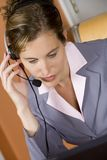 Business Woman. Model Release 352 Woman in early 20s working on computer and talking on headset telephone at home royalty free stock images