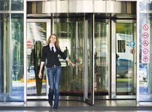 Business woman. Walking out of office tower royalty free stock photo