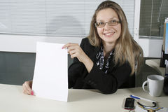 Business woman. Contemporary business woman shows empty sheet of a white paper stock photography
