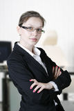 Business woman. Portrait of smiling business woman in cabinet stock image