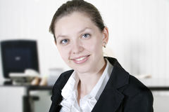 Business woman. Portrait of smiling business woman in cabinet royalty free stock images