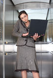 Business woman. On cell phone with computer in lift stock photo