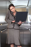 Business woman. On cell phone with computer in lift royalty free stock photography