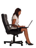Business woman. Sat on an office chair with a laptop computer Stock Image