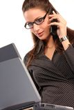 Business woman. Young woman talking on a cell phone and working on a laptop Stock Photo