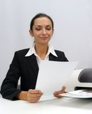 Business woman. Businesswoman is reading next to inkjet printer royalty free stock images