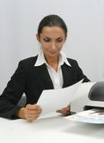 Business woman. Businesswoman is reading next to inkjet printer stock image