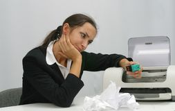 Business woman. Frustrated business woman is trying to install ink cartridge in printer royalty free stock image