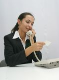 Business woman. On telephone looking at a card Royalty Free Stock Image