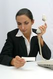 Business woman. Is looking at a card and talking on the phone Stock Photography
