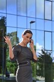 Business woman. Indignant woman talking by phone in front of an office building Royalty Free Stock Image