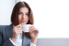 Business woman. Portrait of beautiful young business woman wearing formal clothes drinking coffee while resting at her office near big window stock image