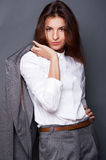 Business woman. Portrait of a beautiful young business woman standing with hand holding jacket behind her shoulder against grey background and posing fashionable stock image